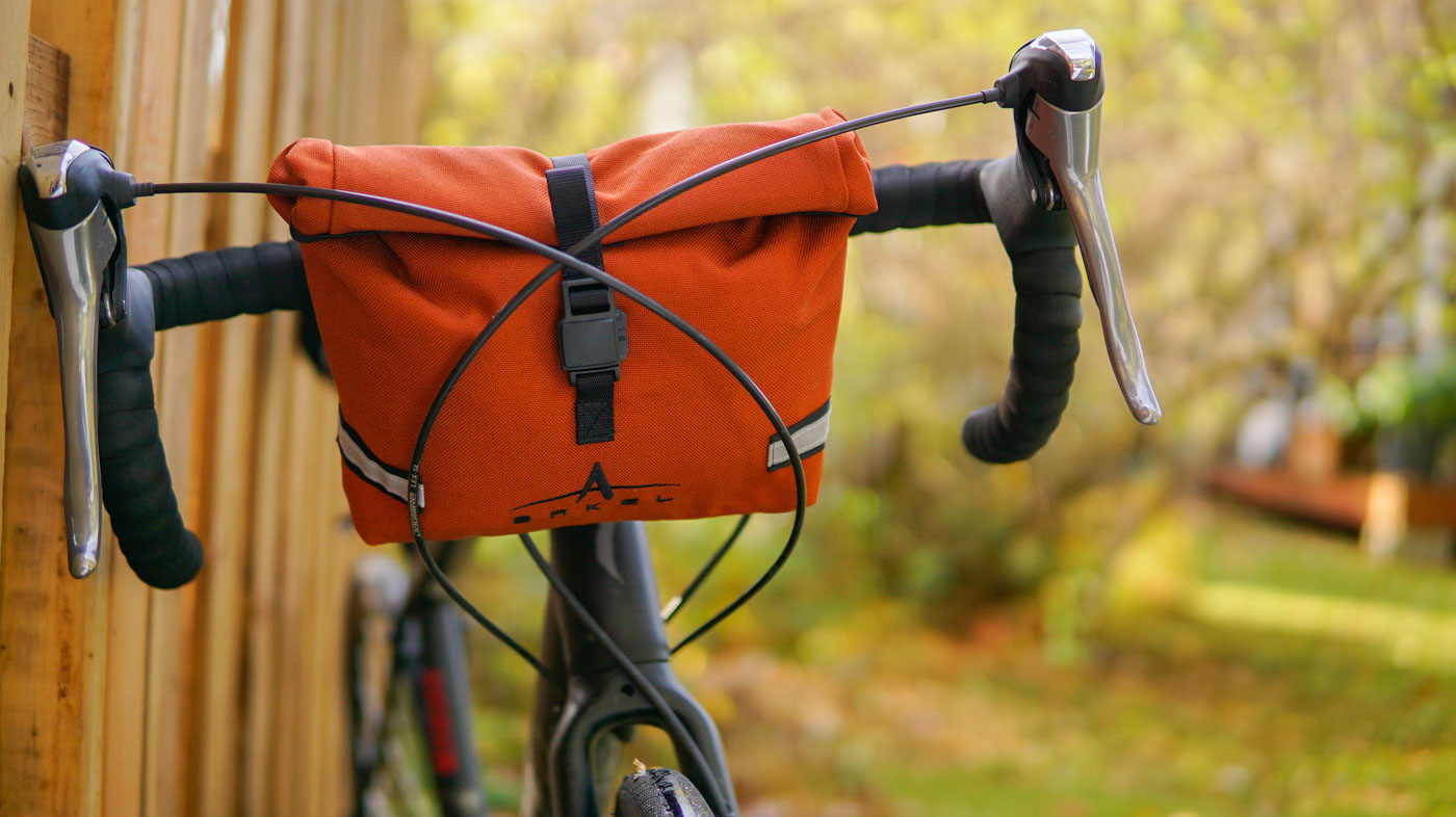 Waterproof handlebar bag Signature BB in the copper color installed on a gravel bike
