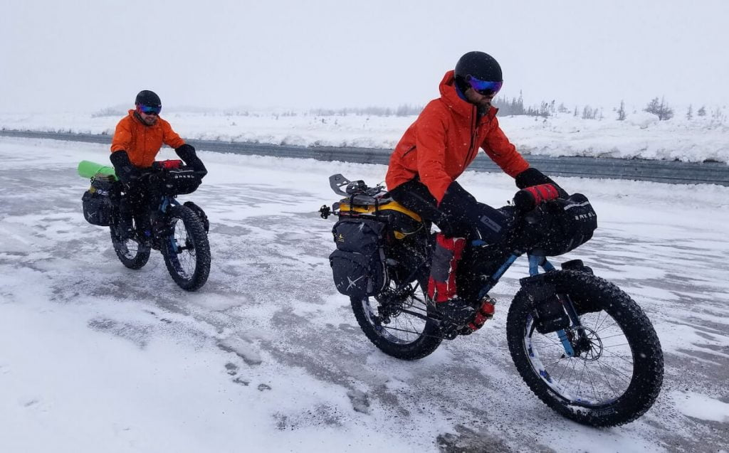 Two Men On Fatbikes Pedaling During Winter In Quebec With Arkel Bags